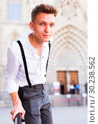Купить «young European guy in shirt and trousers with suspenders walking around city», фото № 30238562, снято 27 июня 2018 г. (c) Татьяна Яцевич / Фотобанк Лори