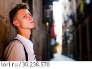 Купить «young European guy in shirt and trousers with suspenders walking around city», фото № 30238570, снято 27 июня 2018 г. (c) Татьяна Яцевич / Фотобанк Лори