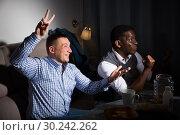 Купить «Positive male interracial friends watching football match on tv», фото № 30242262, снято 26 февраля 2018 г. (c) Яков Филимонов / Фотобанк Лори