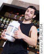 Купить «Attractive sport man holding thumb up and pot of sport supplements», фото № 30242354, снято 28 марта 2018 г. (c) Яков Филимонов / Фотобанк Лори