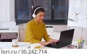 Купить «creative woman in headphones with laptop at office», видеоролик № 30242714, снято 28 февраля 2019 г. (c) Syda Productions / Фотобанк Лори