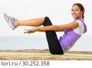 Купить «Woman doing yoga poses on beach by ocean», фото № 30252358, снято 26 мая 2019 г. (c) Яков Филимонов / Фотобанк Лори