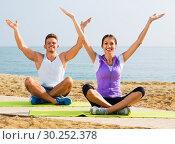Woman and man sitting cross-legged do yoga poses on beach. Стоковое фото, фотограф Яков Филимонов / Фотобанк Лори