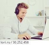 Купить «Young man working in call centre», фото № 30252458, снято 14 декабря 2019 г. (c) Яков Филимонов / Фотобанк Лори
