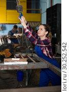 Купить «Portrait of nice female working with lift hook», фото № 30252542, снято 10 октября 2017 г. (c) Яков Филимонов / Фотобанк Лори
