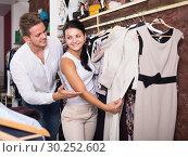 Купить «Adult couple purchasing jacket and dress», фото № 30252602, снято 24 октября 2016 г. (c) Яков Филимонов / Фотобанк Лори