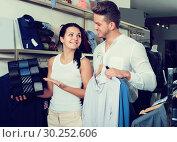 Купить «Cheerful couple chousing jacket, shirt and tie», фото № 30252606, снято 24 октября 2016 г. (c) Яков Филимонов / Фотобанк Лори