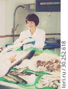 Купить «Mature woman selling chilled fish in store», фото № 30252618, снято 25 октября 2016 г. (c) Яков Филимонов / Фотобанк Лори