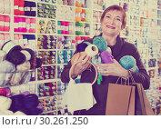 Купить «Woman holding shopping bags and accessories for knitting and embroidery», фото № 30261250, снято 10 мая 2017 г. (c) Яков Филимонов / Фотобанк Лори