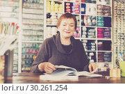 Купить «Woman sits at desc in shop», фото № 30261254, снято 10 мая 2017 г. (c) Яков Филимонов / Фотобанк Лори