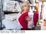 Купить «Mature woman choosing cotton bed cover in the store», фото № 30261434, снято 17 января 2018 г. (c) Яков Филимонов / Фотобанк Лори