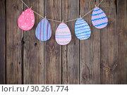 Купить «Paper Easter painted eggs painted hang on clothespins on background old wooden wall.», фото № 30261774, снято 6 марта 2019 г. (c) Майя Крученкова / Фотобанк Лори