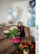 Купить «Красивая женщина средних лет сидит на диване и смотрит вверх. Много цветов и надувные шарики», эксклюзивное фото № 30267486, снято 18 февраля 2019 г. (c) Игорь Низов / Фотобанк Лори