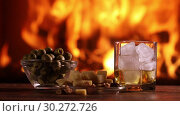 Купить «A man's hand pours whisky from a bottle into a glass on the background of a burning fireplace», видеоролик № 30272726, снято 9 марта 2019 г. (c) Алексей Кузнецов / Фотобанк Лори