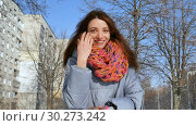 Close up portrait of smiling adult girl in blue coat and colorful knitted scarf during early spring time in the city. Стоковое видео, видеограф Ольга Балынская / Фотобанк Лори
