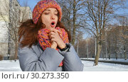 Smiling girl in warm coat and colorful knitted hat and scarf spending time outdoors during sunny day in spring on blue sky background. Стоковое видео, видеограф Ольга Балынская / Фотобанк Лори