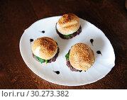 Купить «Three freshly cooked burgers on a white plate top view. Sesame bun, beef cutlet, spinach greens and flowing berry sauce.», фото № 30273382, снято 1 марта 2019 г. (c) Кристина Сорокина / Фотобанк Лори