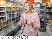 Купить «Thoughtful mature woman among shelves in grocery shop», фото № 30273466, снято 8 февраля 2019 г. (c) Яков Филимонов / Фотобанк Лори