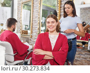 Купить «Young woman hairstylist drying hair with fen of woman client at salon», фото № 30273834, снято 25 апреля 2018 г. (c) Яков Филимонов / Фотобанк Лори