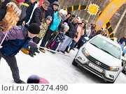 Купить «A man participates in the competition for the holiday Maslenitsa and drags a lightweight LADA car on a rope. City of Cheboksary, Russia, 03/10/2019.», фото № 30274490, снято 10 марта 2019 г. (c) Александр Якимов / Фотобанк Лори