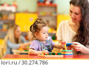 Купить «Babies with teachers playing developmental toys in nursery», фото № 30274786, снято 25 мая 2020 г. (c) Оксана Кузьмина / Фотобанк Лори