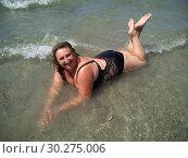Middle-aged woman lies in the sea washed by coastal waves. Стоковое фото, фотограф Дмитрий Морозов / Фотобанк Лори