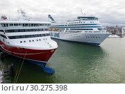 Два современных круизных лайнера в городской гавани облачным мартовским днем. Хельсинки, Финляндия (2019 год). Редакционное фото, фотограф Виктор Карасев / Фотобанк Лори