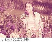 Купить «happy young girl posing near roses and smells flower outdoor», фото № 30275546, снято 18 апреля 2017 г. (c) Яков Филимонов / Фотобанк Лори