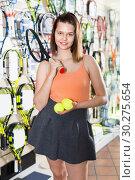 Купить «Female standing in sporting goods store with balls and racket», фото № 30275654, снято 15 мая 2017 г. (c) Яков Филимонов / Фотобанк Лори