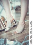 Купить «Girl is trying on brilliant heeled sandals near mirror», фото № 30275702, снято 27 мая 2017 г. (c) Яков Филимонов / Фотобанк Лори