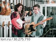 Купить «Smiling female and male teenagers examining electric guitars», фото № 30275710, снято 14 февраля 2017 г. (c) Яков Филимонов / Фотобанк Лори