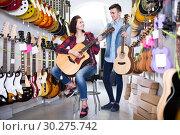 Купить «teenage customers deciding on suitable acoustic guitar in guitar shop», фото № 30275742, снято 14 февраля 2017 г. (c) Яков Филимонов / Фотобанк Лори