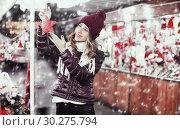Купить «Beautiful young girl choosing Christmas decoration», фото № 30275794, снято 22 декабря 2016 г. (c) Яков Филимонов / Фотобанк Лори
