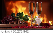 Купить «Still life of a two glasses of sparkling wine and a fruit plate, chocolate and rose on the background of a burning fireplace», видеоролик № 30276842, снято 12 марта 2019 г. (c) Алексей Кузнецов / Фотобанк Лори