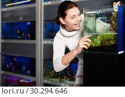 Купить «Girl looking at young fishes in aquarium», фото № 30294646, снято 17 февраля 2017 г. (c) Яков Филимонов / Фотобанк Лори