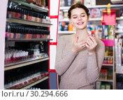 Купить «female customer looking for lipstick in cosmetics shop», фото № 30294666, снято 21 февраля 2017 г. (c) Яков Филимонов / Фотобанк Лори