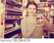 Купить «Glad customer searching for reliable nail polish», фото № 30294674, снято 21 февраля 2017 г. (c) Яков Филимонов / Фотобанк Лори