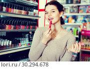 Купить «Smiling woman customer browsing rows of lipstick», фото № 30294678, снято 21 февраля 2017 г. (c) Яков Филимонов / Фотобанк Лори