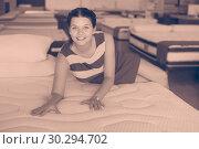 Купить «woman is lying on bed and testing mattress in the store.», фото № 30294702, снято 29 августа 2017 г. (c) Яков Филимонов / Фотобанк Лори