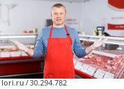 Купить «Smiling man seller offering products in shop», фото № 30294782, снято 22 июня 2018 г. (c) Яков Филимонов / Фотобанк Лори