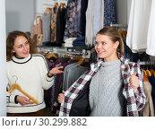 Купить «Woman trying new overcoat», фото № 30299882, снято 6 декабря 2018 г. (c) Яков Филимонов / Фотобанк Лори