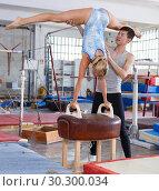 Купить «Man and woman training on pommel horse», фото № 30300034, снято 18 июля 2018 г. (c) Яков Филимонов / Фотобанк Лори