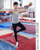 Купить «Man exercising gymnastic action at gym, woman on background», фото № 30300038, снято 18 июля 2018 г. (c) Яков Филимонов / Фотобанк Лори