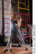 Купить «Young woman in ripped jeans performing pole dance», фото № 30300070, снято 23 мая 2019 г. (c) Яков Филимонов / Фотобанк Лори