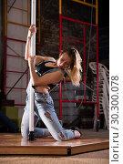 Купить «Young woman in ripped jeans performing pole dance», фото № 30300078, снято 23 мая 2019 г. (c) Яков Филимонов / Фотобанк Лори