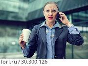 Купить «Adult businesswoman talking on the mobile phone», фото № 30300126, снято 6 мая 2017 г. (c) Яков Филимонов / Фотобанк Лори