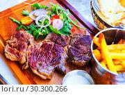 Купить «Beef steak with fried potatoes, sauce and arugula at wooden desk», фото № 30300266, снято 10 октября 2018 г. (c) Яков Филимонов / Фотобанк Лори