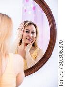 Купить «Young woman looking in the mirror», фото № 30306370, снято 5 июля 2020 г. (c) Яков Филимонов / Фотобанк Лори
