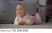 Купить «Indoor portrait of baby girl lying on the belly», видеоролик № 30306698, снято 24 июня 2019 г. (c) Данил Руденко / Фотобанк Лори