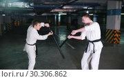 Купить «Two young men in kimono training kendo on a parking lot», видеоролик № 30306862, снято 8 июля 2020 г. (c) Константин Шишкин / Фотобанк Лори